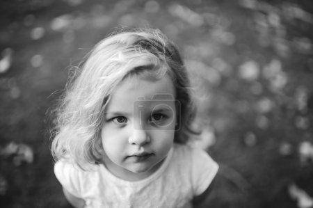 Portrait of a little blond girl outdoors
