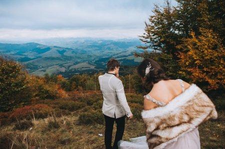 Photo pour Heureux couple nouvellement marié posant dans les montagnes - image libre de droit