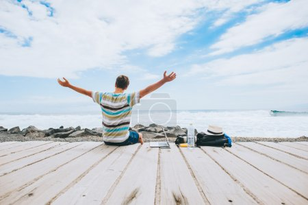 Photo for Handsome young guy the photographer working with a laptop on the beach on sea background - Royalty Free Image