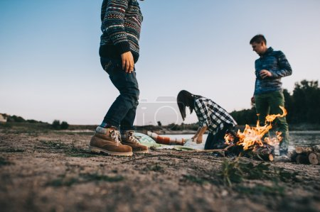 Photo for Happy young family sitting around the campfire on the beach at night fall, mother, father, son - Royalty Free Image