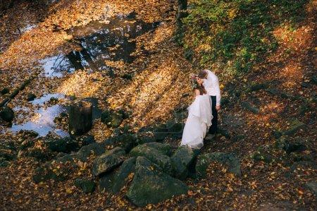 Photo pour Jeune couple en promenade dans la forêt d'automne - image libre de droit