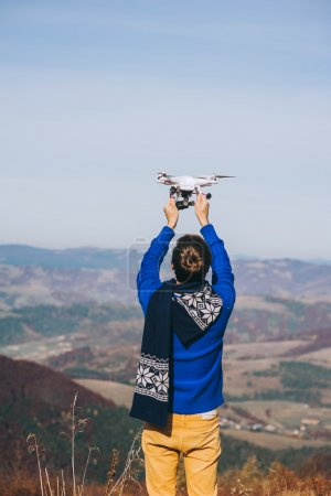 man holding a drone for aerial photography.