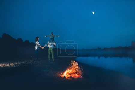 Photo for Happy young family near campfire on the beach at night fall, mother, father, son - Royalty Free Image