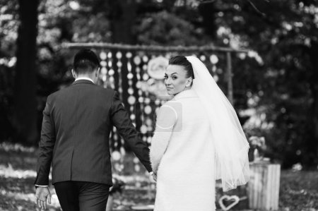 Les nouveaux mariés marchant dans la forêt d'automne