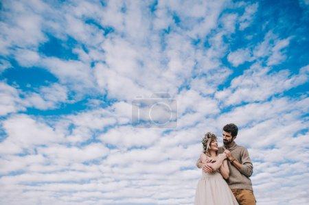 Couple, main dans la main contre le ciel