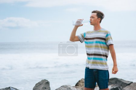 Guy drinking water on the beach