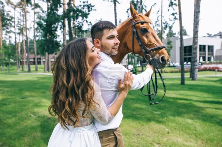 Newlyweds standing next to a horse