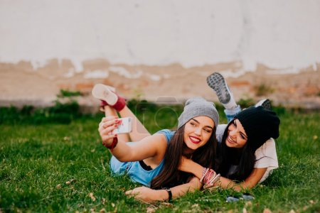 Photo for Pretty young girls taking selfie outdoors - Royalty Free Image