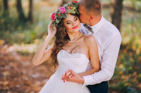 Newlyweds walk in the autumn forest