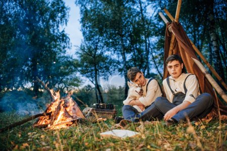 Twin brothers near campfire