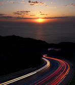 Car lights with sunset and sea in the background.