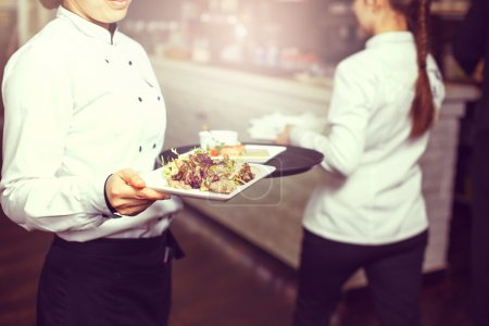 Photo for Waiters carrying plates with meat dish at a wedding - Royalty Free Image