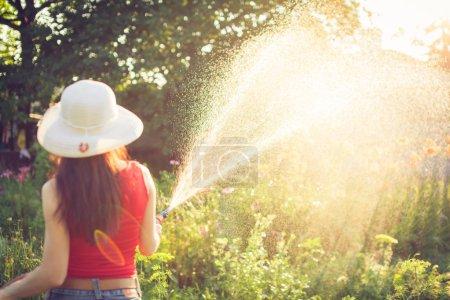 Photo pour Main de femme avec arrosage de tuyau d'arrosage, concept de jardinage - image libre de droit