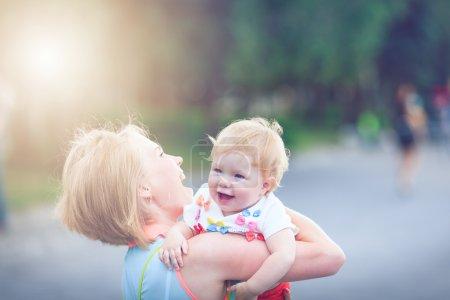 Photo pour Jeune famille heureuse de trois s'amuser ensemble en plein air. Jolie petite fille sur le dos du père. Parents et la fille, l'air heureux et sourire. Bonheur et l'harmonie dans la vie familiale. Plaisir en famille à l'extérieur. - image libre de droit