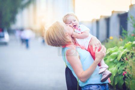 Photo pour Jeune famille heureuse de trois personnes s'amusant ensemble en plein air. Jolie fille sur le dos de son père. Parents et fille ont l'air heureux et sourient. Bonheur et harmonie dans la vie familiale. Plaisir en famille dehors . - image libre de droit
