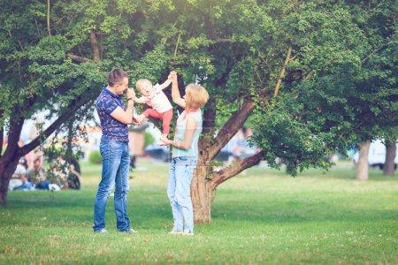 Photo for Young happy family of three having fun together outdoor. Pretty little daughter on her father back. Parents and girl look happy and smile. Happiness and harmony in family life. Family fun outside. - Royalty Free Image