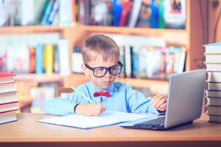 Photo for School Child Boy in Glasses Think in Classroom, Kid Primary Students Reading Book, Pupil Learn Lesson and Dream, Education - Royalty Free Image