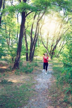 Photo pour Jeune femme en fuite. Femme coureuse traversant la route du parc printanier. Entraînement dans un parc . - image libre de droit