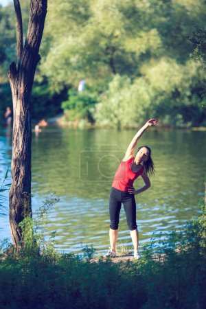 Photo for Woman doing strength exercises at outdoor. Smiling happy doing yoga stretches after running. Fitness model outside in green park on summer day. - Royalty Free Image
