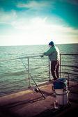 Spinning fisherman on pier