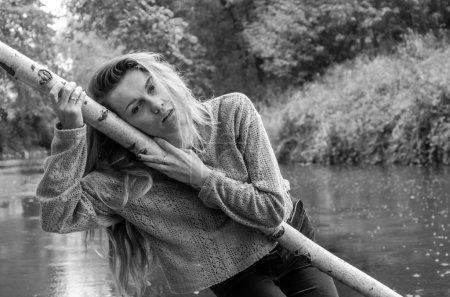 Photo pour Modèle de la belle jeune femme aux longs cheveux blonds assis avec le rire de différentes émotions, la tristesse, chagrin, réflexion sur un pont en bois sur la rive de la rivière et la forêt à la recherche d'eau. - image libre de droit