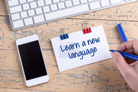 Foto de Moderno teléfono móvil blanco y papel nota con texto aprenden nuevo idioma en el escritorio de madera - Imagen libre de derechos
