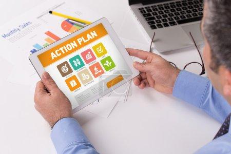 Photo pour Homme d'affaires travaillant sur tablette numérique avec le plan d'action sur un écran - image libre de droit