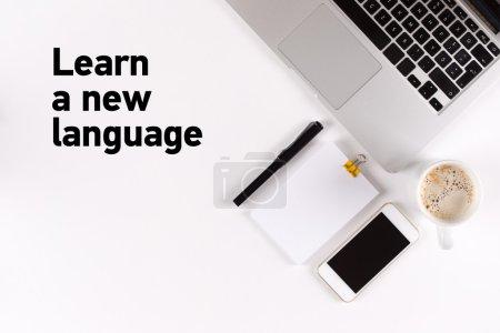 Foto de Aprender del texto nuevo en el escritorio con ordenador portátil, teléfono, taza y copia espacio - Imagen libre de derechos