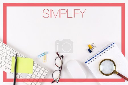 Photo for High angle view of various office supplies on desk with text simplify - Royalty Free Image