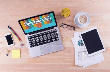 Photo pour Ordinateur portable avec texte bestseller sur écran et autres objets sur le bureau, le concept d'affaires - image libre de droit