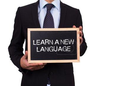 Foto de Empresario celebración mini pizarra con aprende un nuevo mensaje de la lengua - Imagen libre de derechos