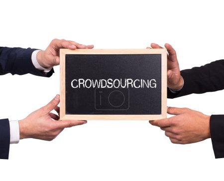 Photo pour Deux hommes d'affaires détenant mini tableau noir avec le message de crowdsourcing - image libre de droit