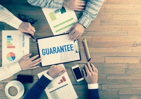 Photo pour Équipe des activités siégeant sur table avec texte presse-papiers et garantie à ce sujet - image libre de droit