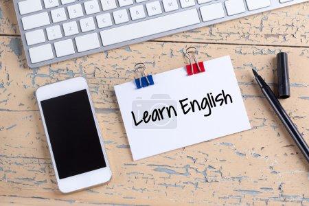 Photo pour Note de papier avec texte apprendre anglais et smartphone avec clavier sur le bureau en bois - image libre de droit