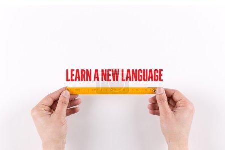 Foto de Las manos masculinas con la regla y texto aprenden un nuevo idioma - Imagen libre de derechos