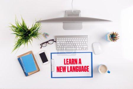 Foto de Escritorio de oficina con aprender un nuevo texto en portapapeles, papeles y otros objetos alrededor, vista superior - Imagen libre de derechos