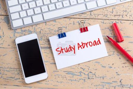 Photo pour Téléphone portable et note papier sur le bureau avec des études de texte à l'étranger - image libre de droit