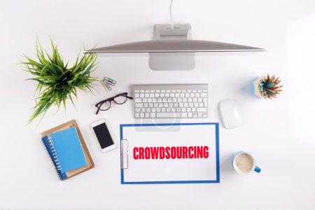 Photo pour Bureau avec le crowdsourcing texte sur le presse-papiers, documents et autres objets autour, vue de dessus - image libre de droit
