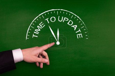Photo pour Homme d'affaires pointant sur ardoise verte avec temps de texte mise à jour - image libre de droit