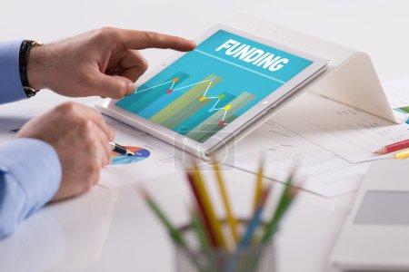 Photo pour Homme d'affaires travaillant sur tablette avec du texte de financement sur un écran - image libre de droit