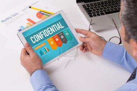 Photo pour Homme d'affaires travaillant sur tablette avec texte confidentiel sur un écran - image libre de droit