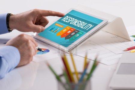 Photo pour Homme d'affaires travaillant sur tablette avec du texte de responsabilité sur un écran - image libre de droit