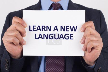 Foto de Papel de hombre de negocios que muestra con texto aprender un nuevo idioma - Imagen libre de derechos