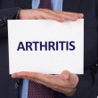 Businessman showing paper with text arthritis