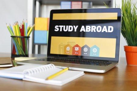 Photo pour Ordinateur portable sur bureau en bois avec des objets et des études de texte à l'étranger - image libre de droit