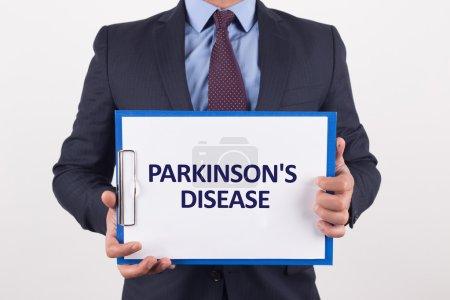 Photo pour Homme d'affaires montrant papier avec texte la maladie de Parkinson - image libre de droit