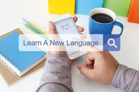 Foto de Hombre sentado en el escritorio con teléfono móvil en las manos y la barra de búsqueda con texto aprende un nuevo idioma - Imagen libre de derechos