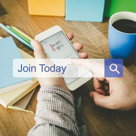 Photo pour Homme assis sur le bureau avec téléphone portable dans les mains et la barre de recherche avec join texte aujourd'hui - image libre de droit
