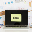 Sticky note with text chaos pasted on the laptop s...