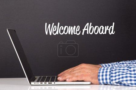 Photo pour Mâle mains sur clavier d'ordinateur portable avec texte Bienvenue à bord - image libre de droit